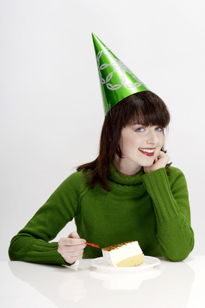 Woman with party hat eating cake photo