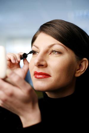 Businesswoman applying mascara photo
