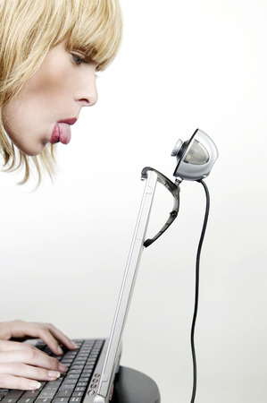 Woman sticking out her tongue at a webcam while using laptop photo