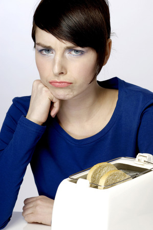 impatience: Frustrated woman waiting for her toast Stock Photo