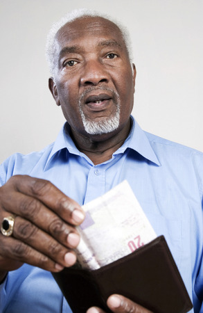 Senior man taking out money from his wallet photo