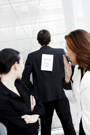 Businessman with a kick me sign on his back