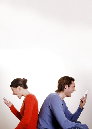 Couple screaming into mobile phone photo