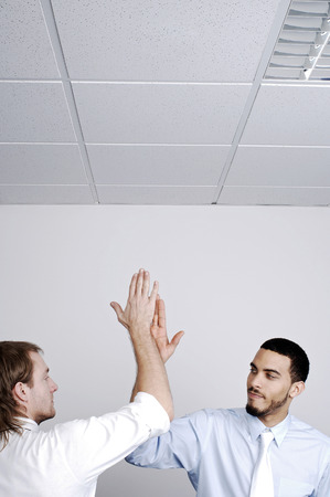 Businessmen giving high five photo