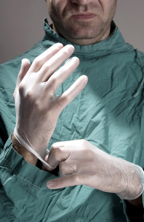 operation gown: Doctor wearing surgical gloves