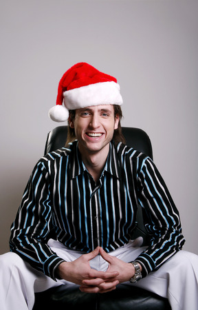 Businessman with Christmas hat sitting on the chair smiling photo