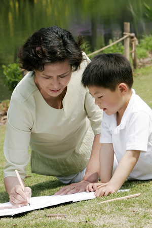 Grandmother and grandson painting picture in the park photo
