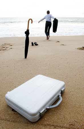 Businesswoman running to the sea leaving her things behind photo
