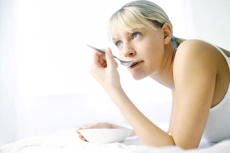 Woman daydreaming while eating on the bed photo