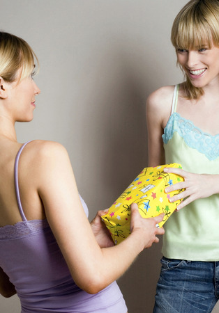 Woman receiving present from her friend photo
