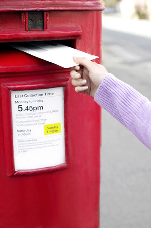 Hand putting a letter into the post box photo