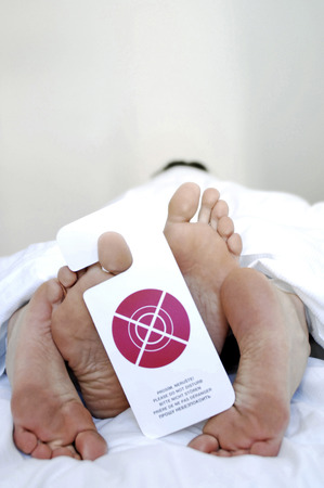 Couple on the bed with a sign hanging from the toe photo