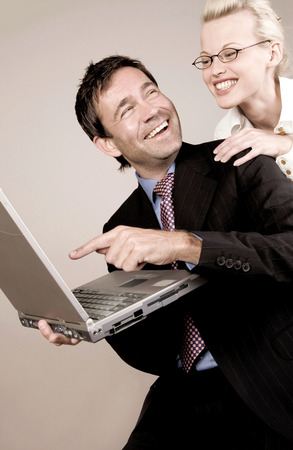 Business people laughing while using laptop photo