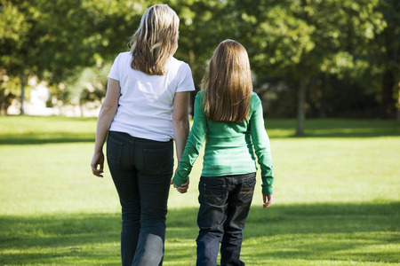 Mother and daughter holding hands while walking in the park photo