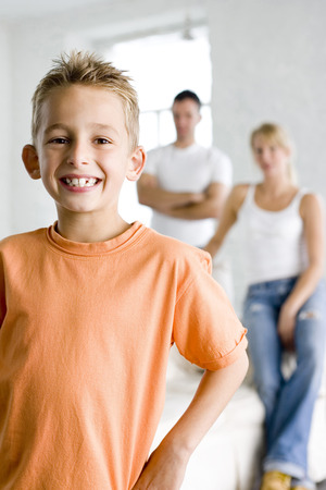 Boy smiling at the camera with his parents in the background photo