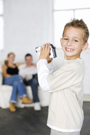 Boy filming parents with camcorder Stock Photo