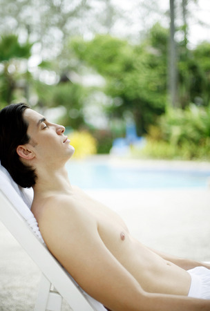 bare chested: A bare-chested man relaxing beside a swimming pool