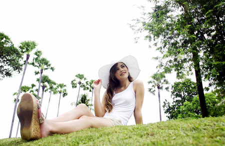 A young lady sitting on the grass Imagens