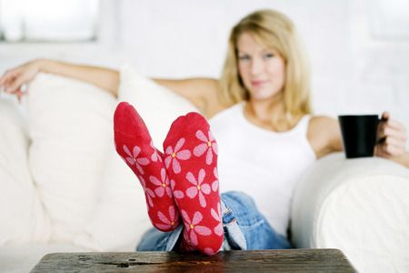 Mature lady wearing a pair of red flowery sock photo