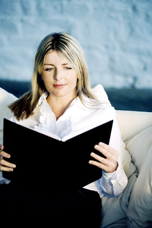 A business lady reading on a couch Imagens