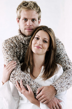 Man hugging his wife, looking at the camera