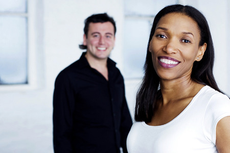 A guy standing behind a young woman