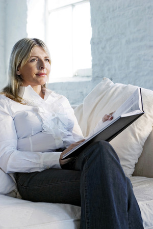 A confident looking business lady sitting on a couch Imagens