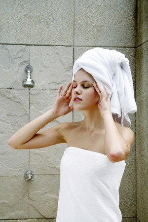 towel wrapped: Woman with towel wrapped hair massaging her head in the bathroom