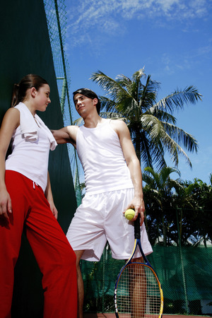 Man talking to woman in the tennis court photo