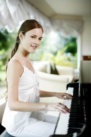 tocando el piano: Mujer tocando el piano en su casa Foto de archivo