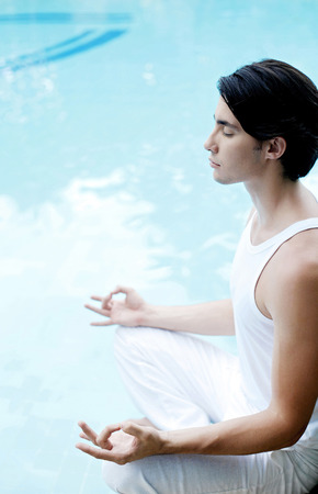 Man meditating by the pool side photo