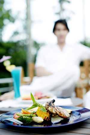 mouthwatering: Focus on a mouth-watering meal with a man sitting in the background Stock Photo
