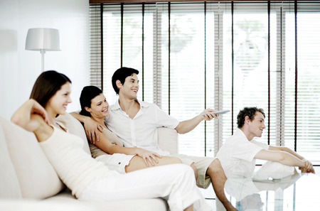 Men and women watching television at home photo