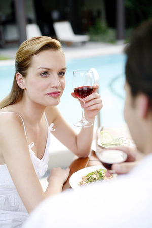 Woman holding a glass of red wine while talking to her boyfriend photo