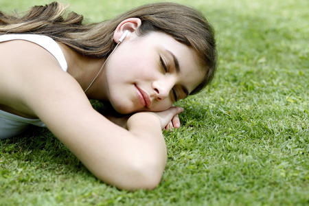 Woman lying forward on the grass listening to music photo