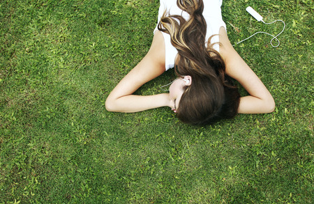 lying forward: Woman lying forward on the grass listening to music Stock Photo