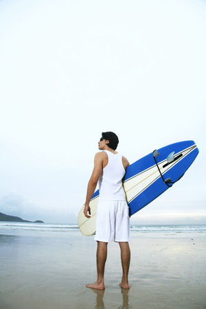 Man with sunglasses holding a surfboard on the beach photo