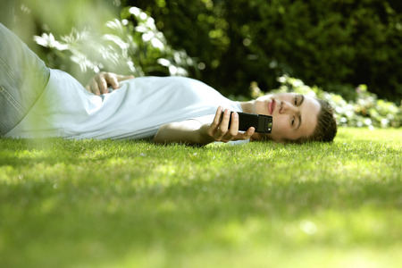taking nap: Teenage boy lying on the field taking his own picture with camera phone Stock Photo