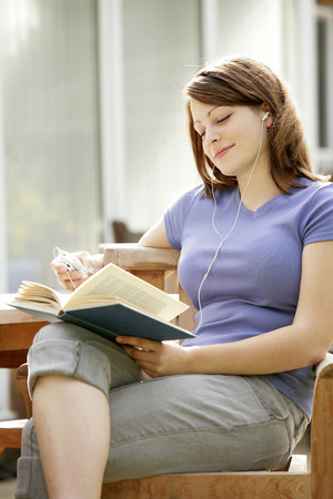 revision book: Teenage girl listening to music while reading book Stock Photo