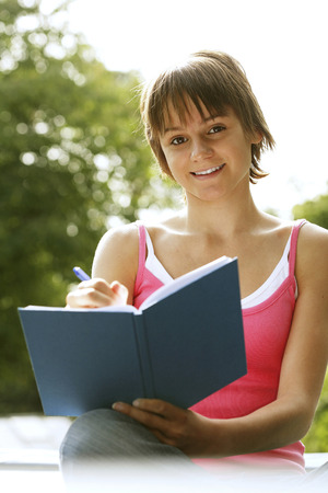 revision book: Teenage girl writing journal Stock Photo