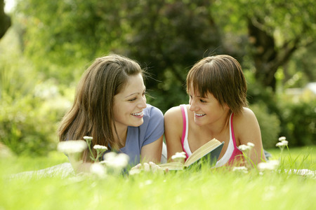 lying forward: Teenage girls lying forward on the field reading book