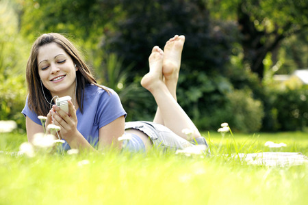 Teenage girl lying forward on the field listening to music on a portable MP3 player photo