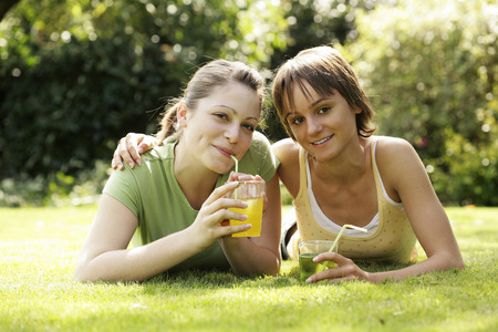 Teenage girls lying forward on the field enjoying their drinks photo