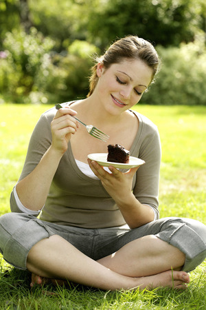Teenage girl sitting on the field enjoying a piece of cake photo