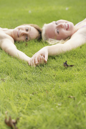 girls holding hands: Teenage girls holding hands while lying on the field