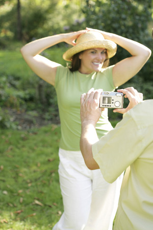taking a wife: Man taking picture for his wife in the park Stock Photo