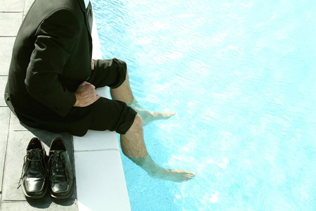 Businessman sitting by the pool side with his legs in the pool photo