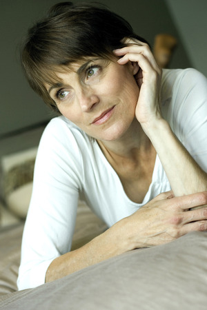 lying forward: Woman lying forward on the bed daydreaming