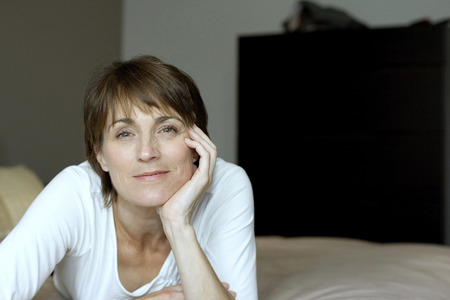 Woman lying forward on the bed smiling at the camera photo