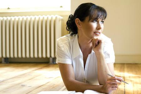 lying forward: Woman lying forward on the floor thinking while writing